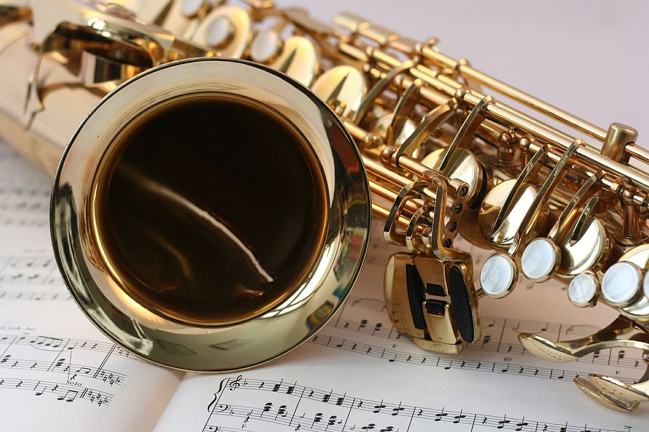 A gold saxophone on top of sheet music
