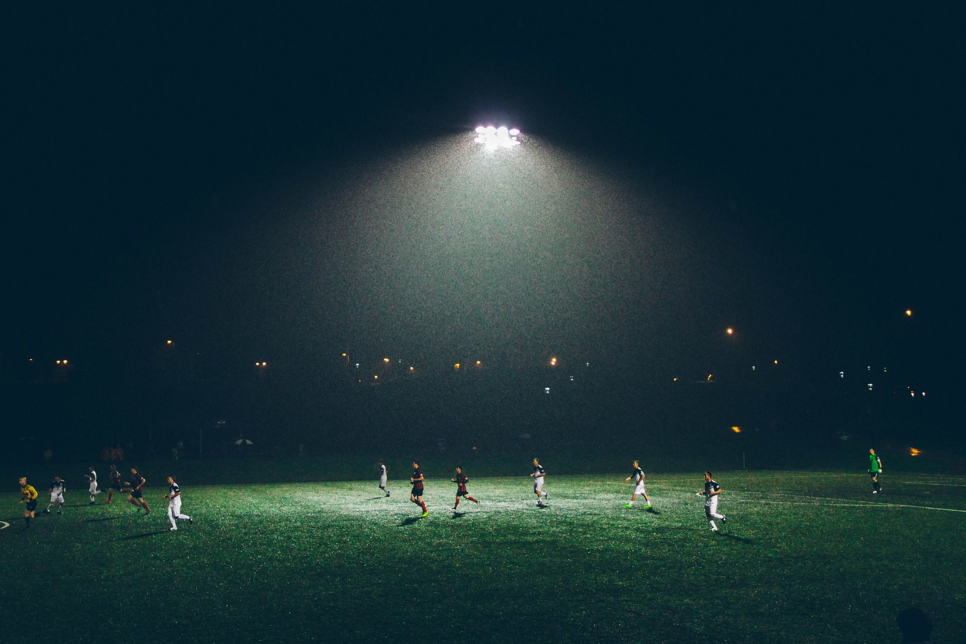 Soccer players on a field at night